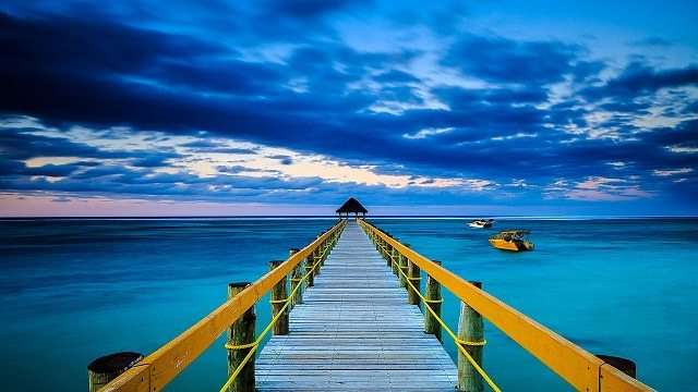 Blue ocean underneath wooden pier Full HD Wallpaper